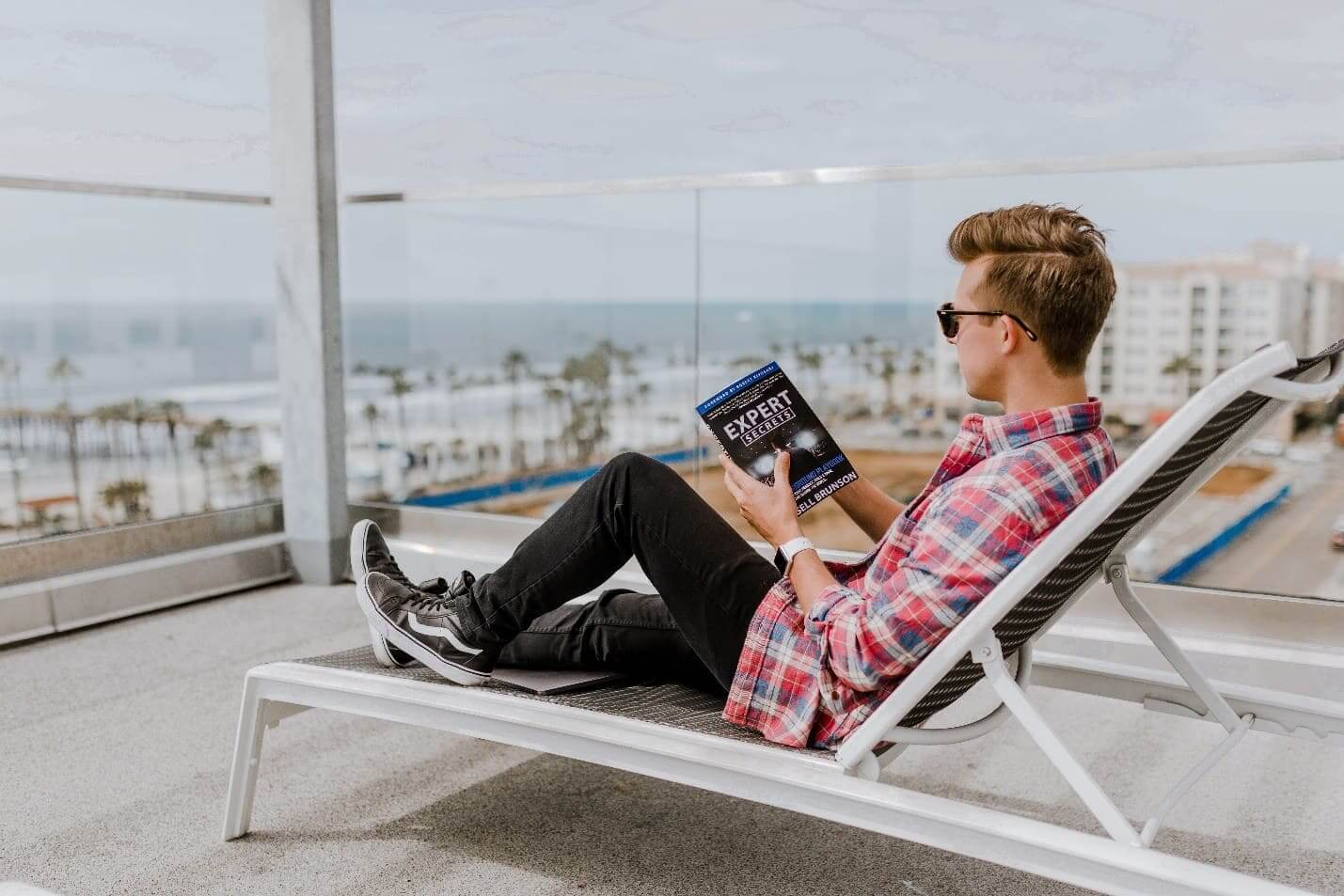 man sitting lounge chair reading a book photo