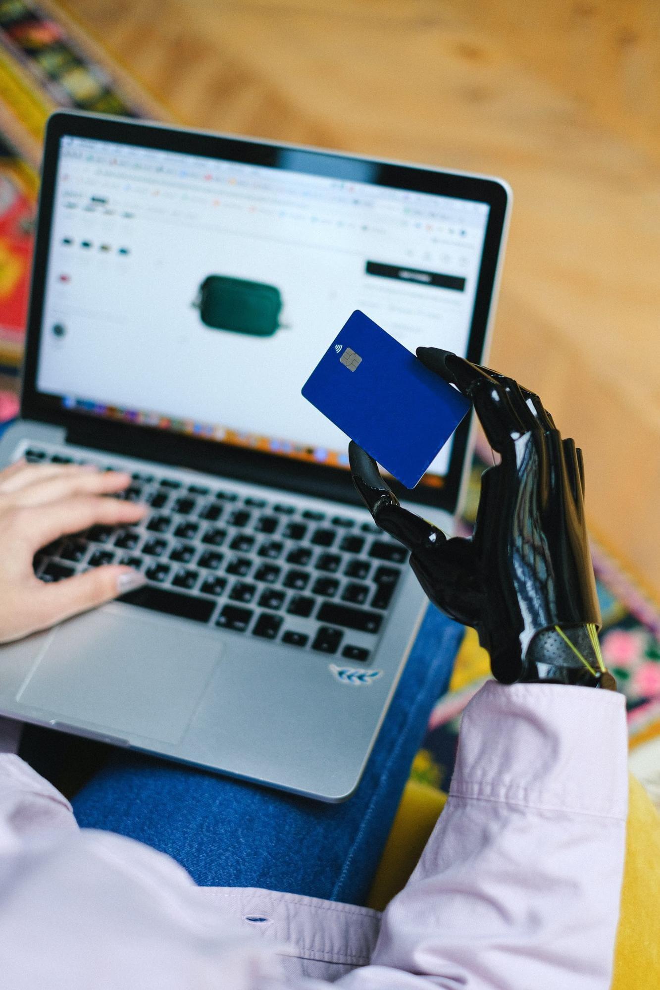 mão robótica segurando um cartão em frente a um laptop.