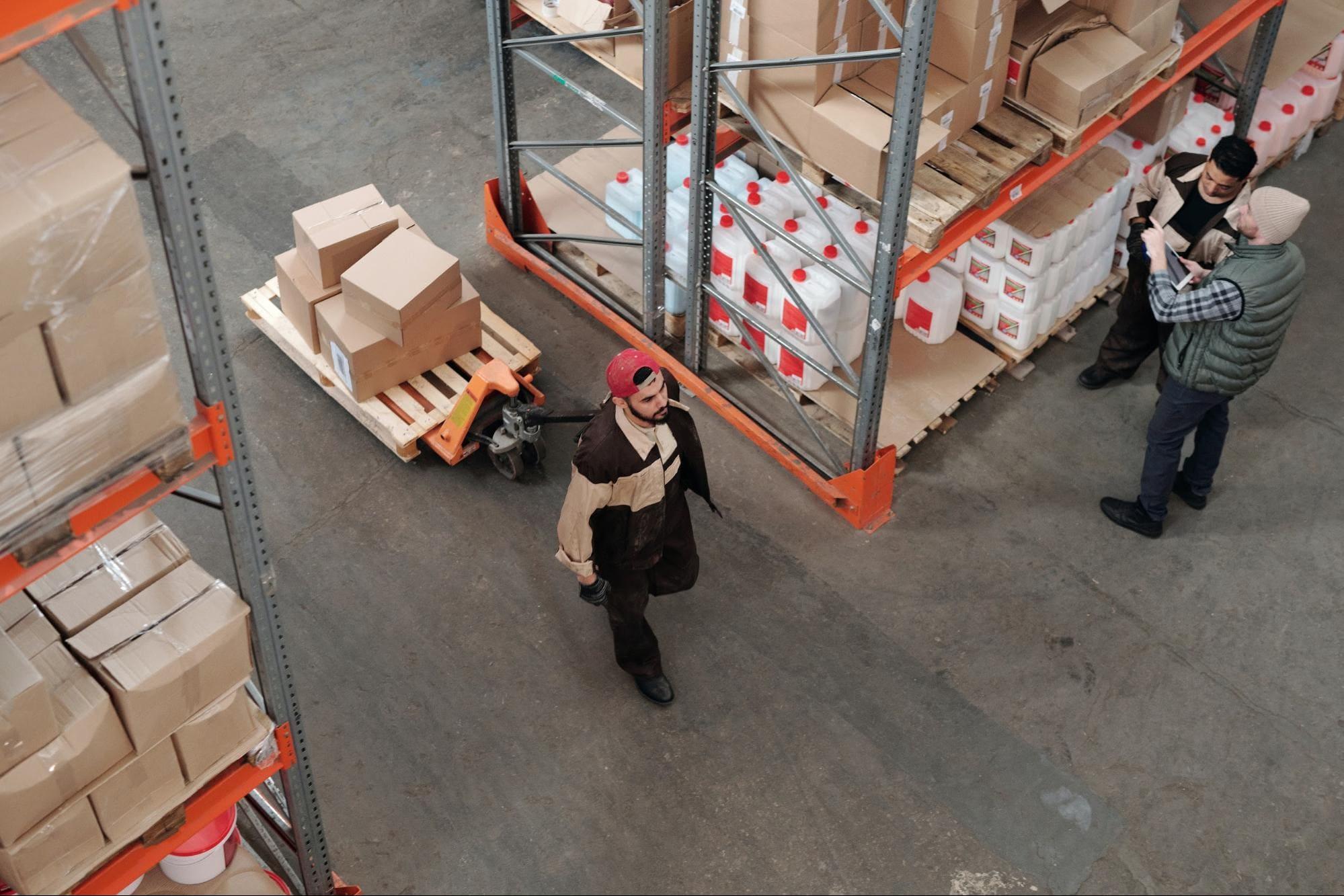 Imagem de um estoque com caixas sendo transportadas em um carrinho de mão