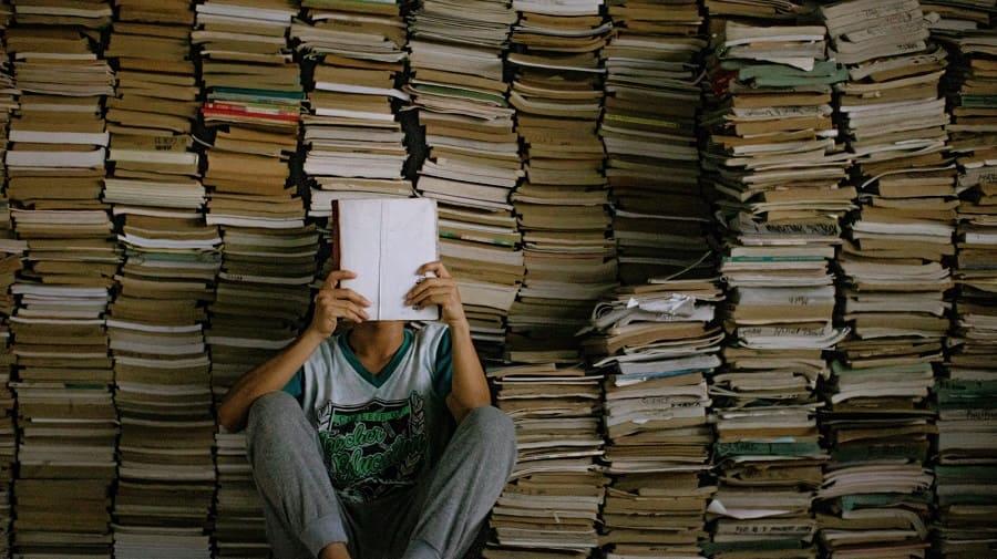 Foto de uma pessoa lendo em frente a uma pilha de livros