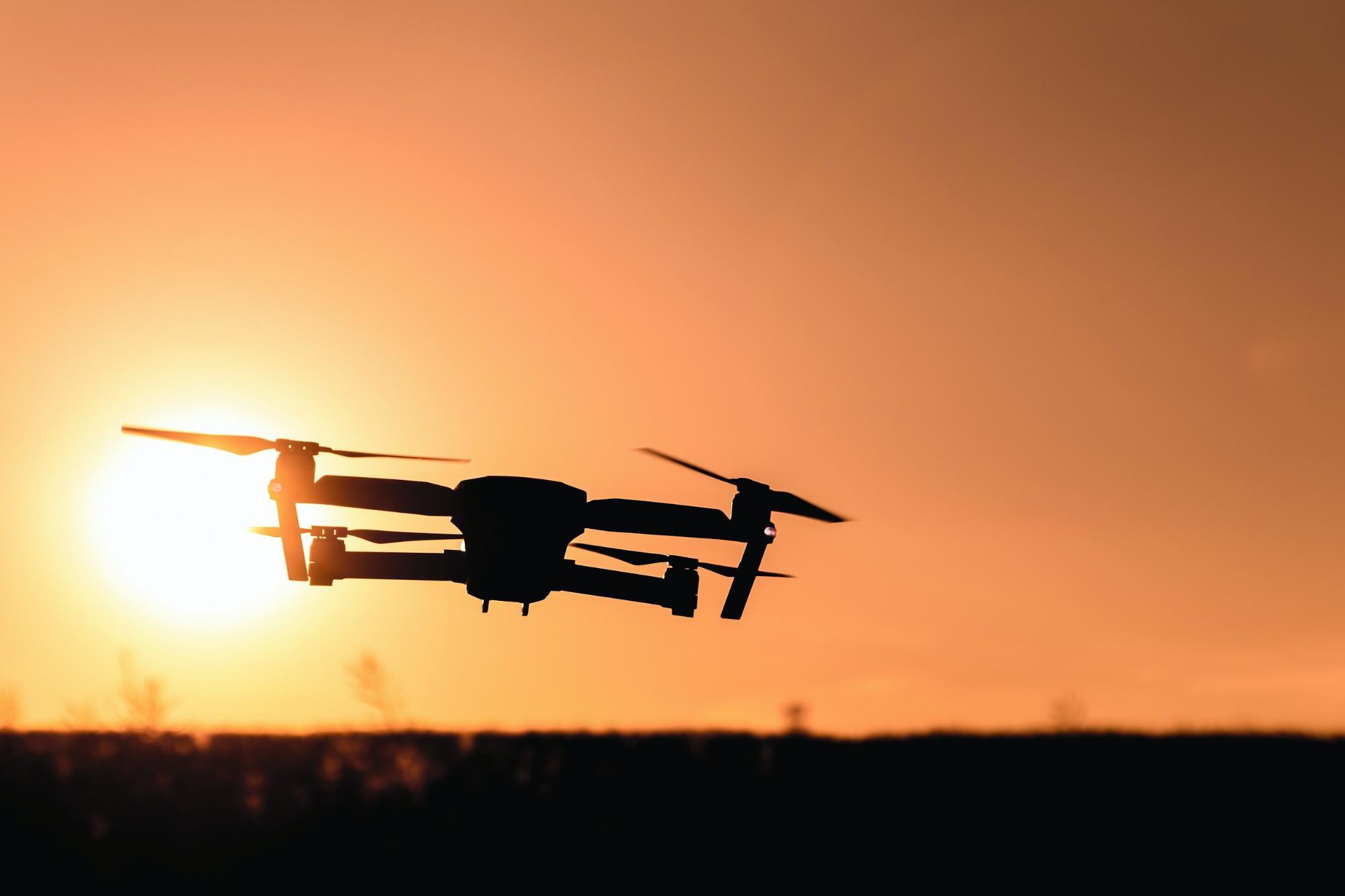 imagem de um drone voando com por-do-sol ao fundo.