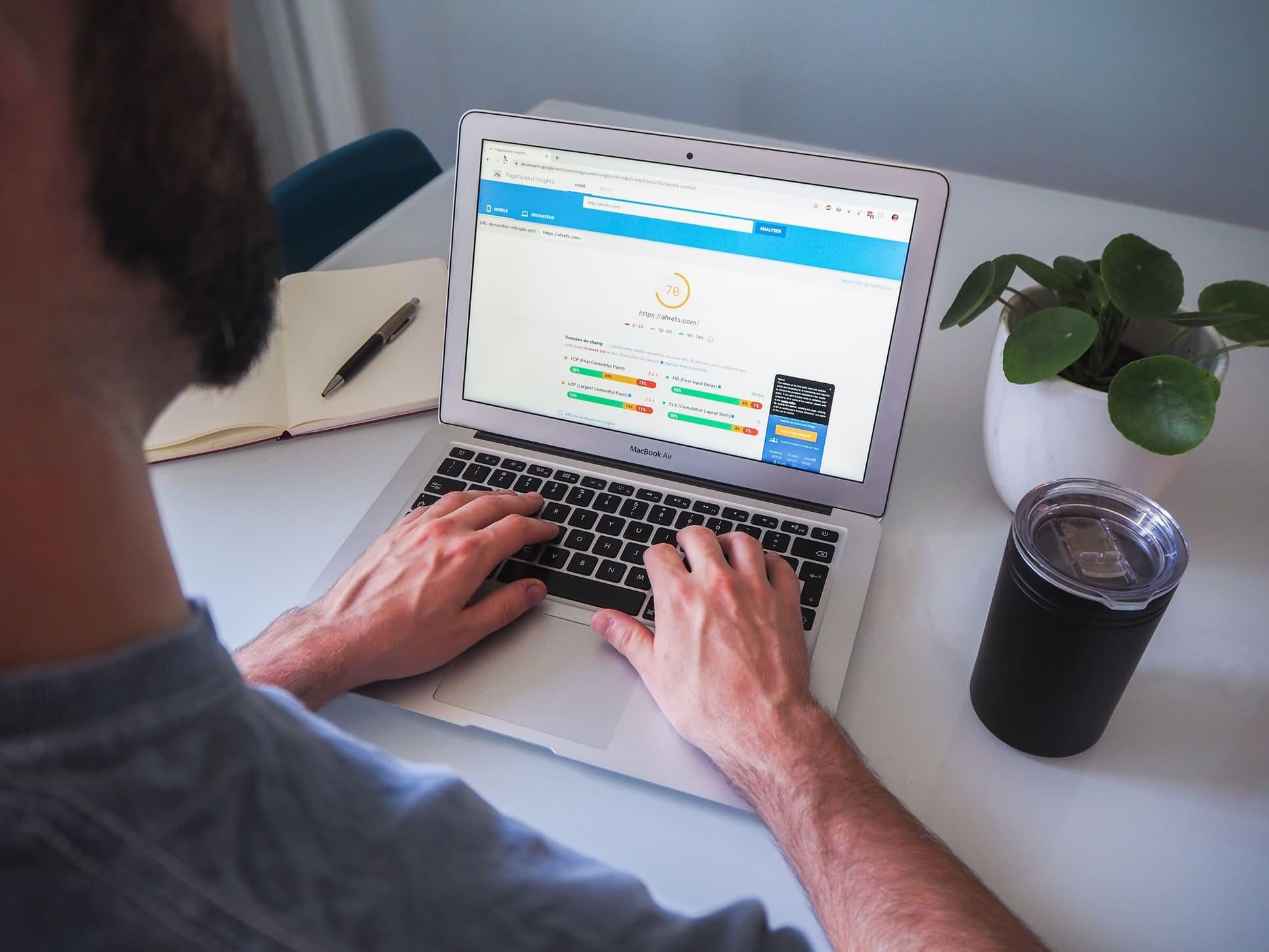 Imagem de uma pessoa usando a ferramenta Ahrefs em um computador